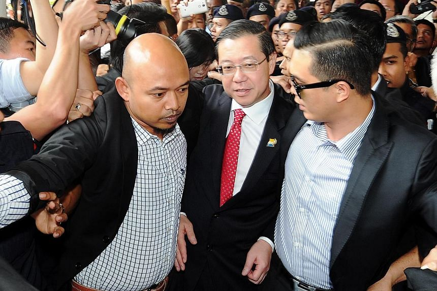 Lim (centre), the chief minister of Penang, being escorted by Malaysian Anti-Corruption Commission officers to the High Court in George Town yesterday. Behind him (partially hidden) is Phang, the accused businesswoman. Hundreds of people outside the