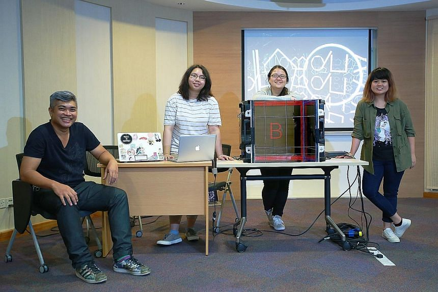 (From far left) Mentor Zullikhan Abdullah and interactive media programme participants Hazel Sim, Carissa Chew and Tok Jin Yu with a mock-up of the 360-degree enclosed cube installation that will be shown in front of Ngee Ann City Civic Plaza.