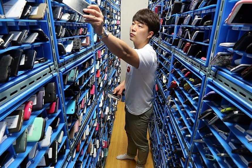 A worker putting away lost smartphones at the Mobile Phone Lost and Found Centre in Seoul on Thursday. Run by the Korea Association for ICT Promotion and the nation's three mobile networks, the facility keeps the devices for nine months, says the wor