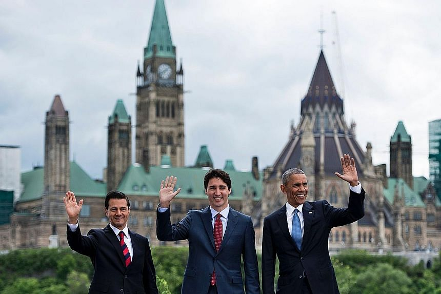 (From left) Mexican President Enrique Pena Nieto, Canadian Prime Minister Justin Trudeau and US President Barack Obama posing for a group photo with Canada's Parliament Hill in the background during the North American Leaders' Summit on Wednesday in