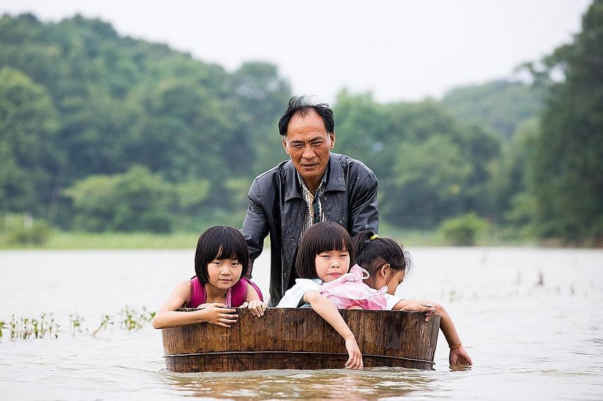 A man pushing a tub carrying children as he gets them back home after school due to massive flooding in Duchang, Jiangxi province, China, on Monday. Heavy rains in the region disrupted train services, made highways impassable, and forced thousands of