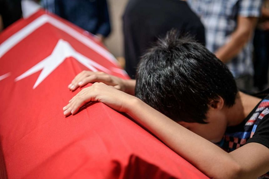 A child leans on the coffin of his uncle, suicide attack victim Hamidullah Safar on June 30, 2016 in Istanbul.