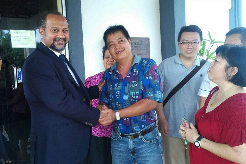 Mr Moo He Hong shakes the hand of his lawyer Mr Gobind Singh Deo after the court ruling in Negeri Sembilan, Malaysia, on July 1, 2016. Mr Moo's son and wife - Mr Moo Wee Keong (bespectacled) and Madam Kuek Soo Lan (in red blouse) - stand next to him.