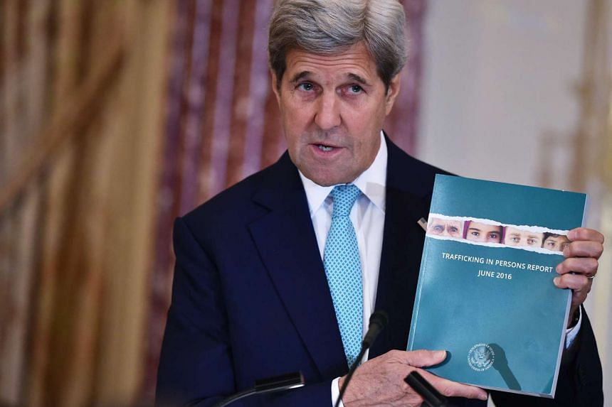 US Secretary of State John Kerry holds a copy of the 2016 Trafficking In Persons Report during its release on June 30, 2016.