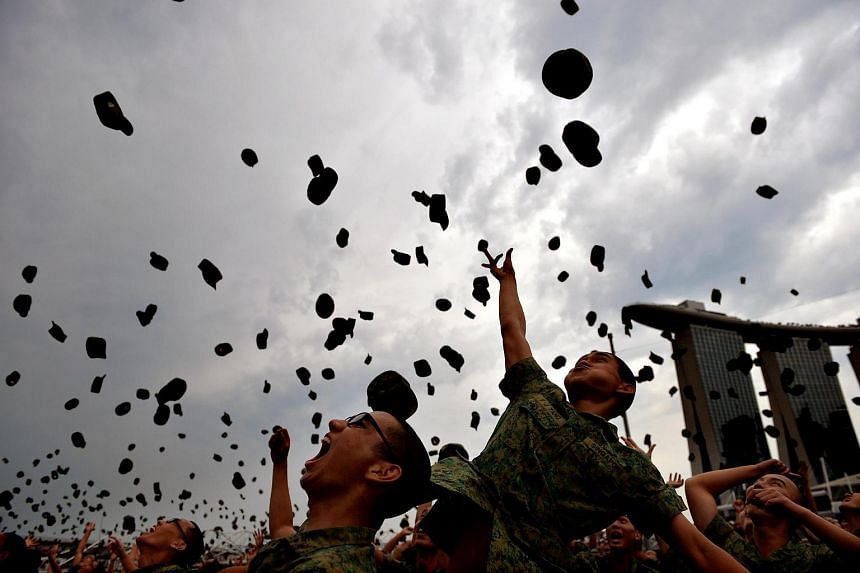 Soldiers throwing their jockey caps in the air to celebrate the end of their basic military training on April 12, 2014.
