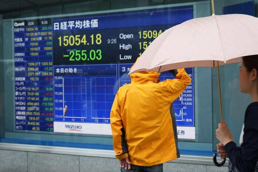 Pedestrians look at share prices from the Tokyo Stock Exchange in Tokyo on June 28.