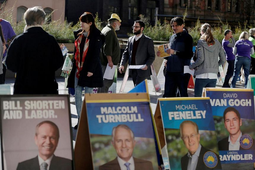 Early voters in Australia's July 2 general election walk to a polling centre past banners promoting Labour leader Bill Shorten (left) and Liberal Party Prime Minister Malcolm Turnbull at Sydney's Town Hall on June 29.