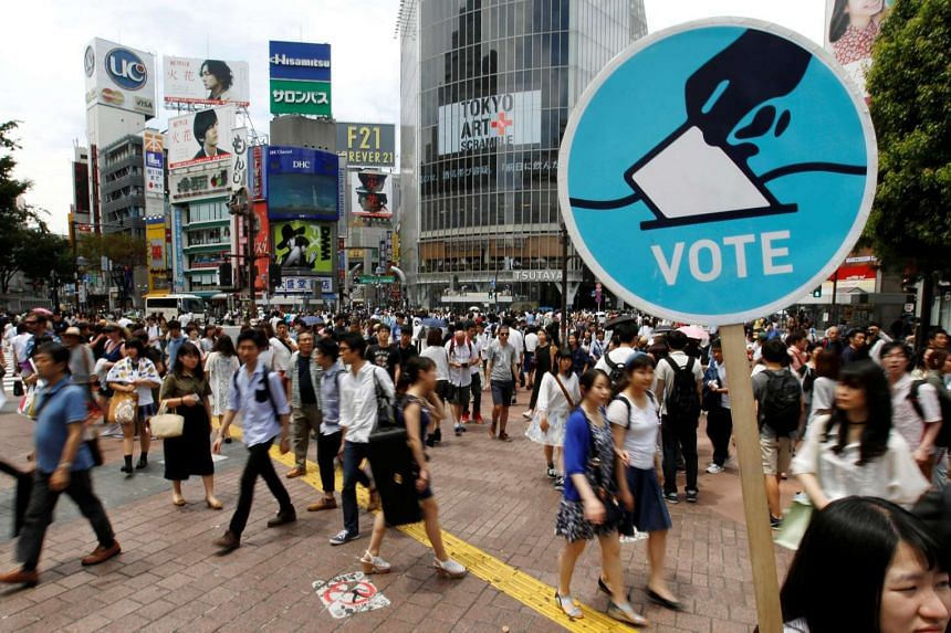 A member of the Students Emergency Action for Liberal Democracy holds a placard calling on youths to vote in the upper house election in Shibuya, Tokyo on June 26.