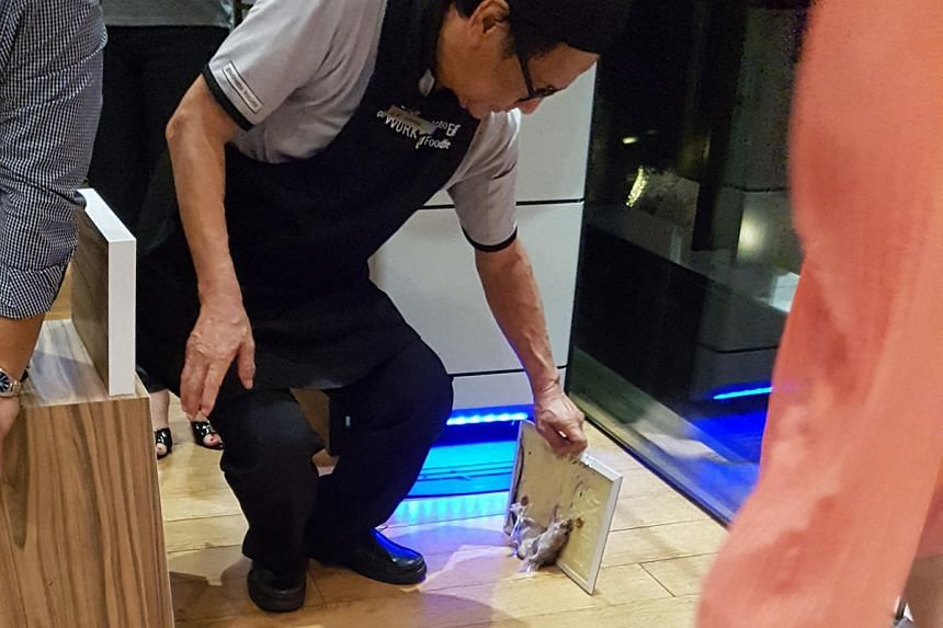 A rat trap with a live rat in it fell from the ceiling of a Marina Bay Financial Centre food court.