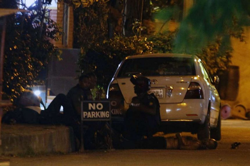 Bangladeshi police officers take cover as a man lies on the ground near the Holey Artisan Bakery.