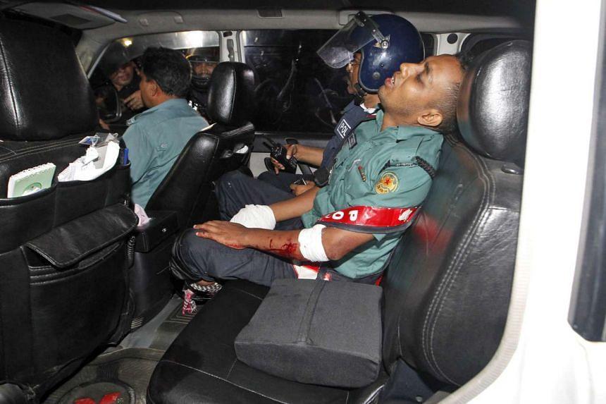 An injured police officer sits in a car after suffering wounds from a crude bomb set off by the gunmen.
