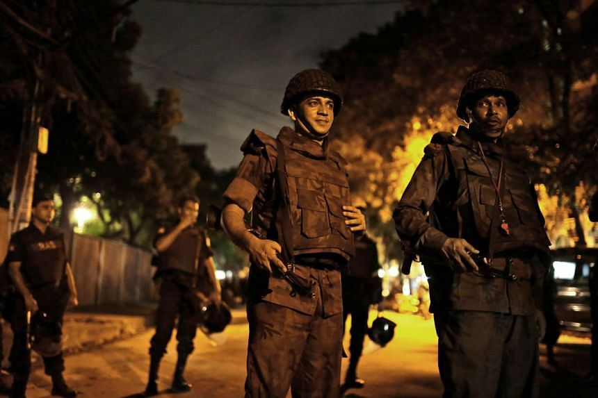 Bangladeshi security forces stand guard as they seal off the streets close to the scene of the hostage-taking.