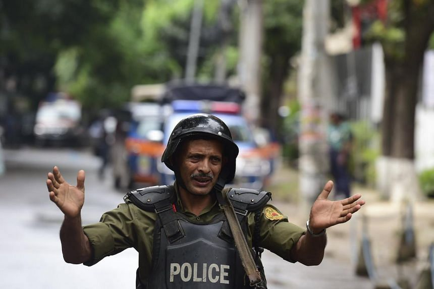 A Bangladeshi police officer gestures during a rescue operation as gunmen take position in a restaurant in the Dhaka's high-security diplomatic district on July 2.