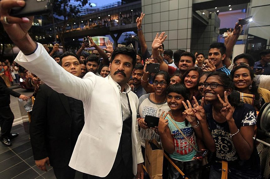 Stars from the Tamil and Malayalam film industries such as singer Vijay Yesudas (left) and Vedhika (above) took wefies with fans as they walked the red carpet last night at the South Indian International Movie Awards. Hundreds of fans clamoured for t