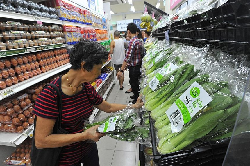 Housewife Yap Lai Choo, 75, browsing Value Fresh brand vegetables at a FairPrice Shop that opened yesterday in Eunos Crescent. The vegetables under this new FairPrice brand are 5 per cent to 10 per cent cheaper than the items from the supermarket cha