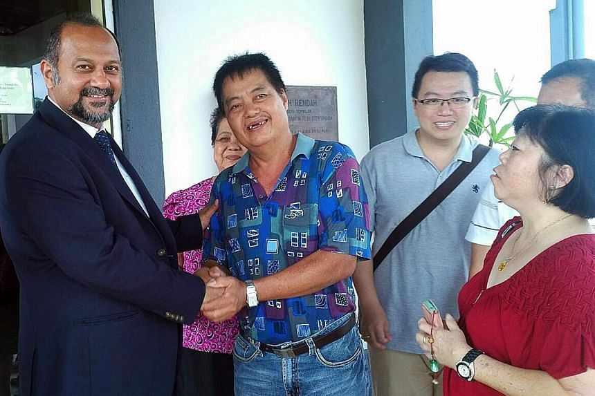 Mr Moo He Hong shaking the hand of his lawyer Gobind Singh Deo yesterday after the court ruling. Mr Moo's wife and son, Madam Kuek Soo Lan (in red blouse) and Mr Moo Wee Keong (bespectacled), are with them.
