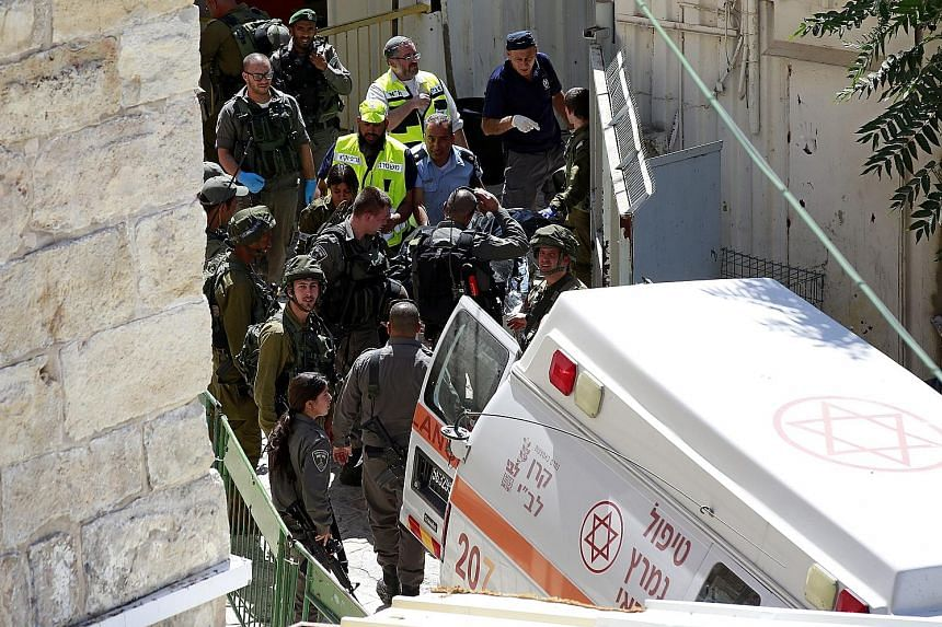Troops carrying the body of a Palestinian woman who, Israeli police said, was shot dead after trying to stab an Israeli guard in the West Bank city of Hebron.