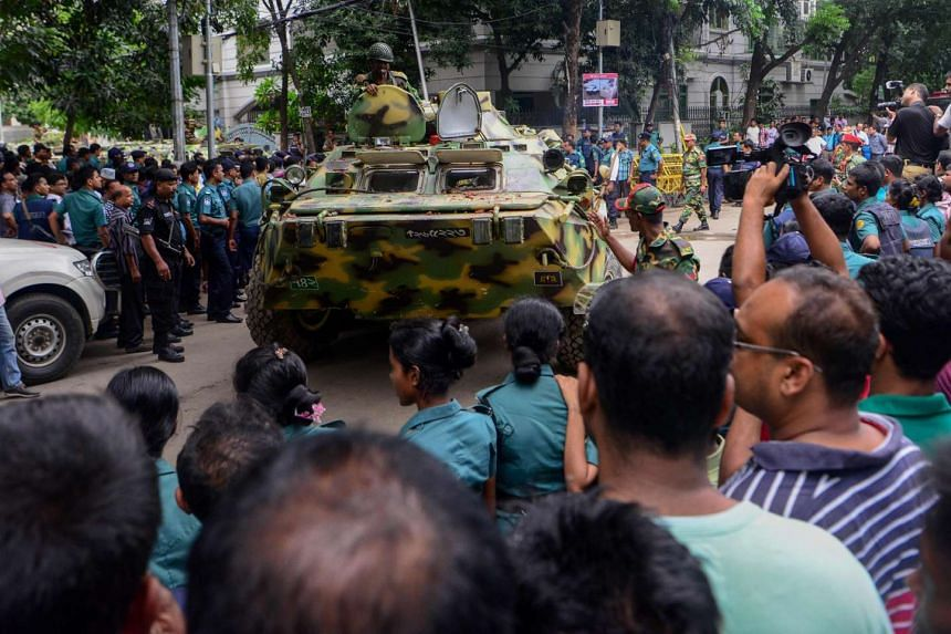 A Bangladeshi armoured military tank makes its way past journalists, onlookers and police near the scene of the seige.