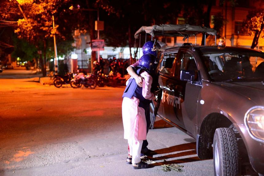 A wounded police personnel is helped by a colleague, after gunmen stormed the Holey Artisan restaurant and took hostages, in the Gulshan area of Dhaka, Bangladesh on July 1.