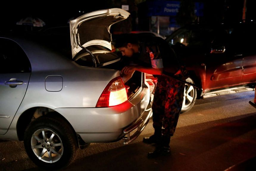 Security personnel check vehicles after gunmen stormed the Holey Artisan restaurant and took hostages in the Gulshan area of Dhaka, Bangladesh, on July 2.