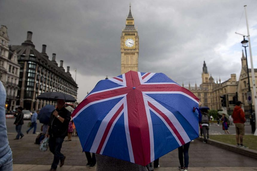 A pedestrian shelters from the rain beneath a Union flag themed umbrella as they walk near the Big Ben clock face and the Elizabeth Tower at the Houses of Parliament in central London on June 25.