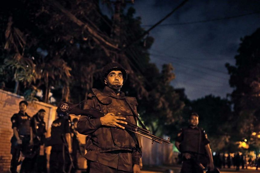 Bangladeshi security forces stand guard as they seal off the streets near a Spanish resturant, following a hostage taking, in Dhaka, on July 1, 2016.
