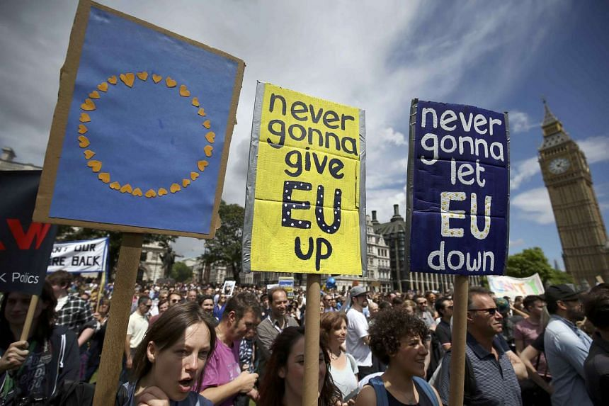 "Protestors hold banners in Parliament Square at a ""March for Europe"" demonstration against Britain's decision to leave the EU, in London, on July 2, 2016."