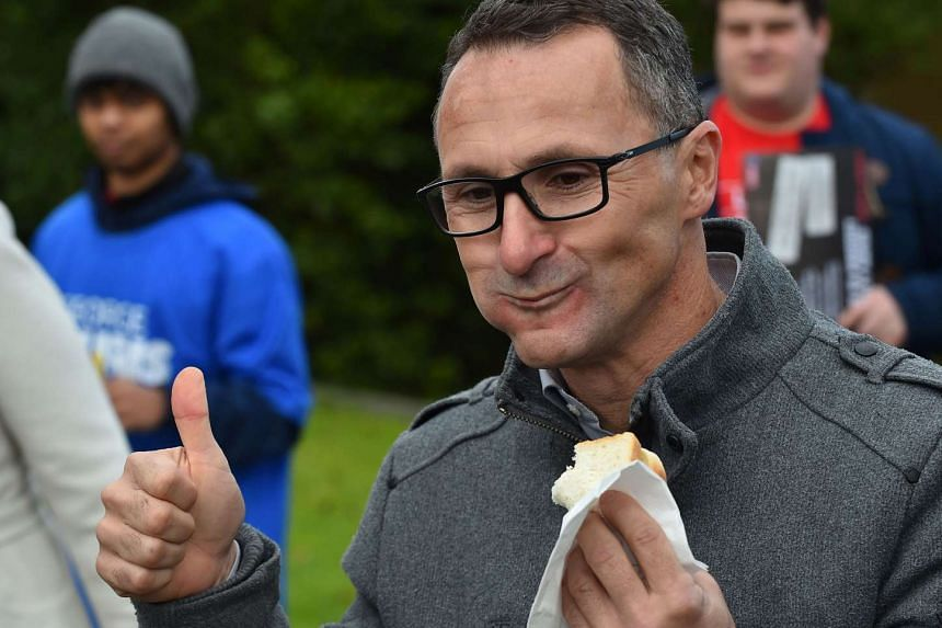 Leader of the Australian Greens Party Richard Di Natale celebrates the freedom of democracy with a thumbs up after biting into a sausage after casting his vote in the Australian Federal Election.
