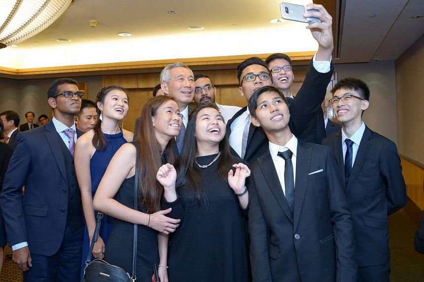 Prime Minister Lee Hsien Loong takes a wefie with scholarship recipients at the IES 50th Anniversary Gala Dinner on July 1.