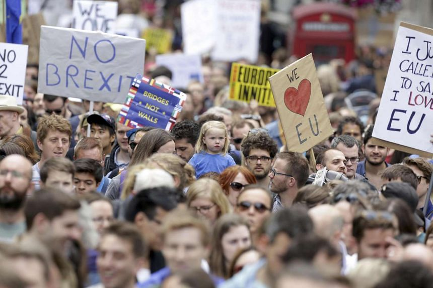 """People hold banners during a """"March for Europe"""" demonstration against Britain's decision to leave the EU."""