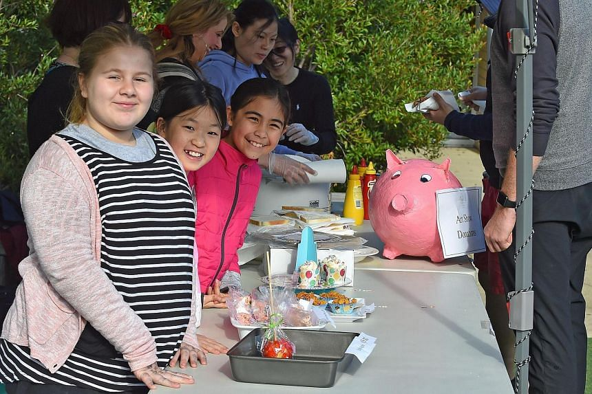Local primary school children in the inner city suburb of Richmond happily sell cakes, lollies and sausages to people as they wait in line to cast their vote in the Australian Federal Election in Melbourne on July 2.