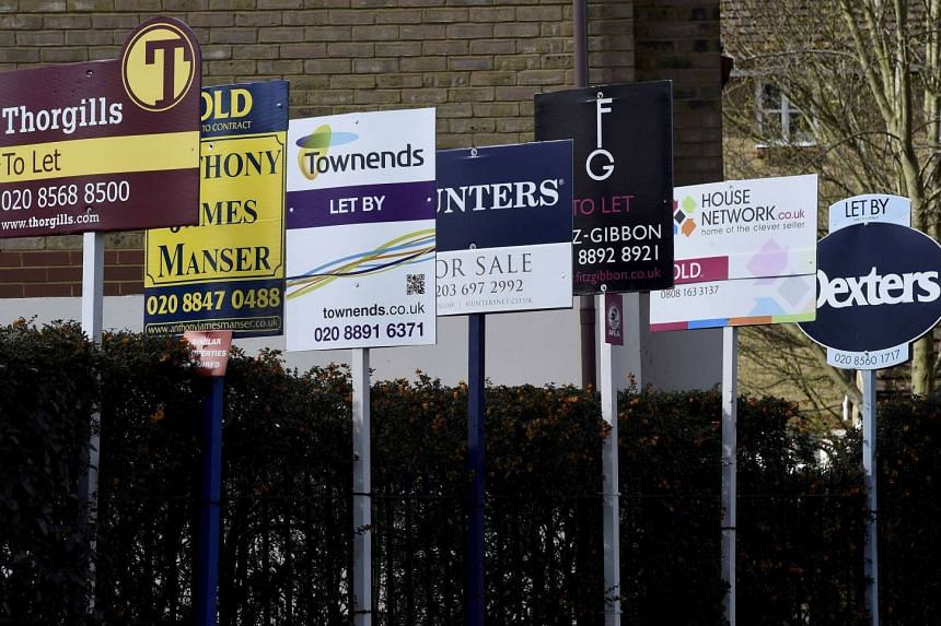 Property estate agent sales and letting signs are seen attached to railings in London, Britain, March 30, 2016.