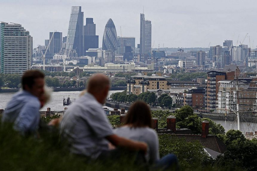 The skyline of the City of London is pictured on the horizon as people relax in Greenwich park in south-east London on June 26.