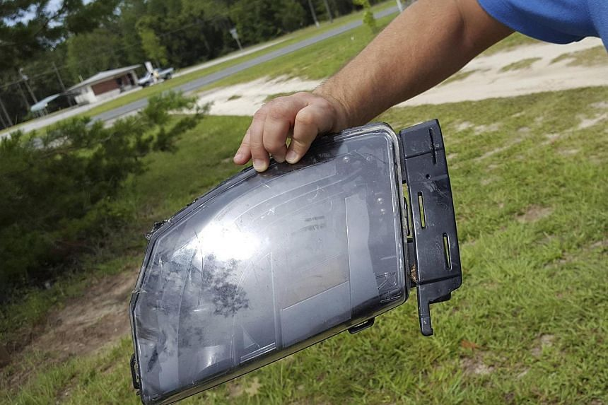 Robert VanKavelaar shows a piece of the Tesla car found in his property where the car came to rest when its driver was killed in a collision with a truck in May in Williston, Florida, on July 1.