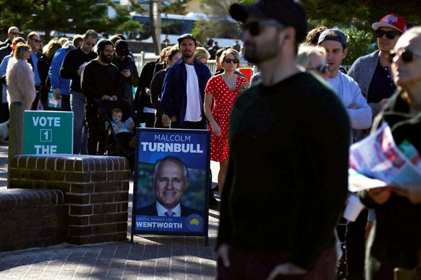 Voters stand in a line as they enter the voting station located in the South Bondi Lifesaving Club, at Sydney's Bondi Beach, Australia, on July 2.
