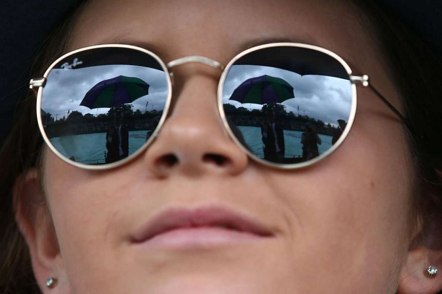 A steward holding an umbrella is reflected in the sunglasses of a Wimbledon tennis tournament spectator in London on July 1, 2016.