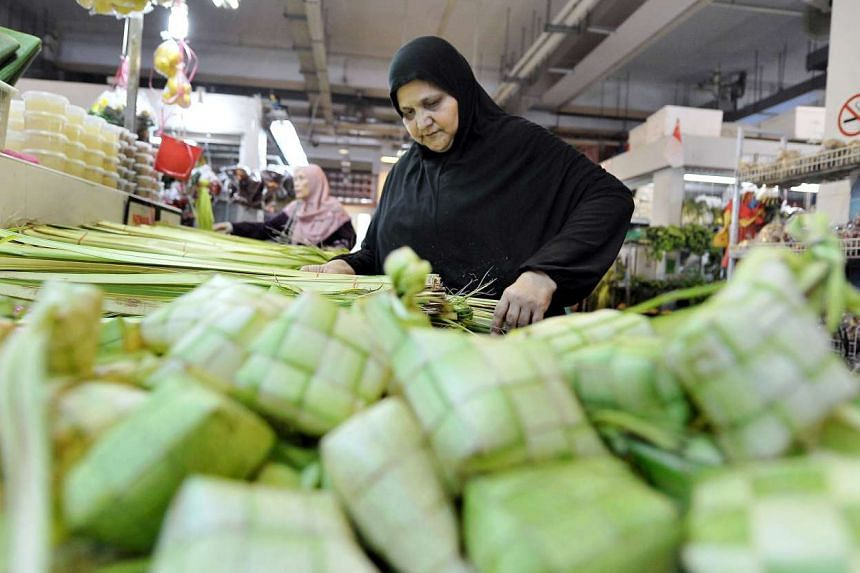 A stall assistant packs the coconut leaves, or janur, used to make ketupat for sale at the Geylang Serai bazaar.