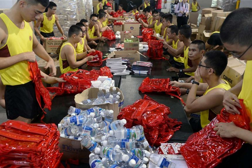 Full-time National Service men pack National Day Parade fun packs into boxes at Kranji Camp 3 on July 29, 2016.