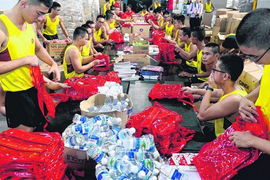 Full-time National Service men pack National Day Parade fun packs at Kranji Camp 3 on June 29, 2016.