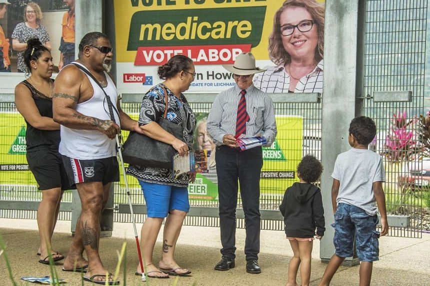 Australian voters queue up in front of a political billboard about Medicare, in Edmonton, Queensland, on July 2, 2016.