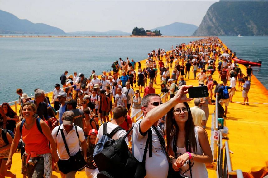 People take selfies on the art installation 'The Floating Piers' on Lake Iseo, in northern Italy, on July 2, 2016.