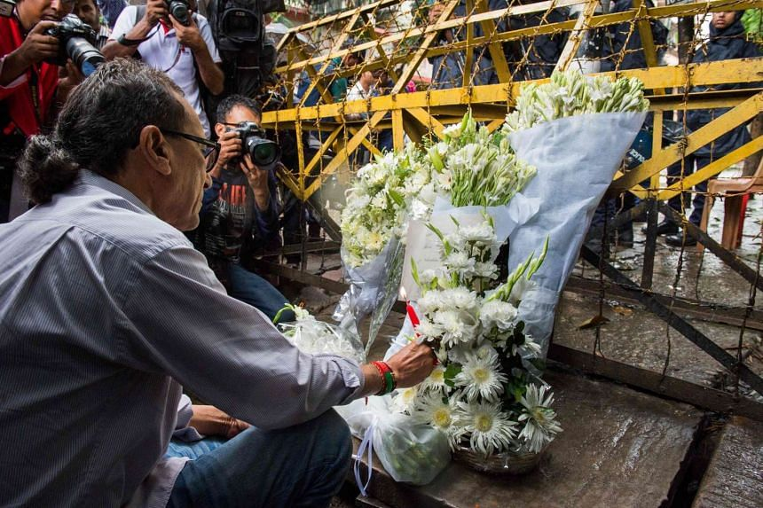 A Bangladeshi social activist lights a candle on floral arrangement that he placed on July 3, 2016 on a road block in Dhaka leading to an upscale cafe that was the site of a bloody siege.