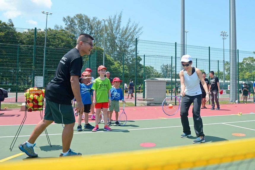 Minister for Culture, Community and Youth Grace Fu trying her hand at tennis during the launch of the ActiveSG tennis academy, on July 3, 2016.