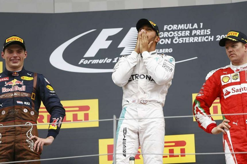 Lewis Hamilton of Britain (centre) poses after the race, flanked by Max Verstappen of Netherlands (left) and Kimi Raikkonen of Finland.