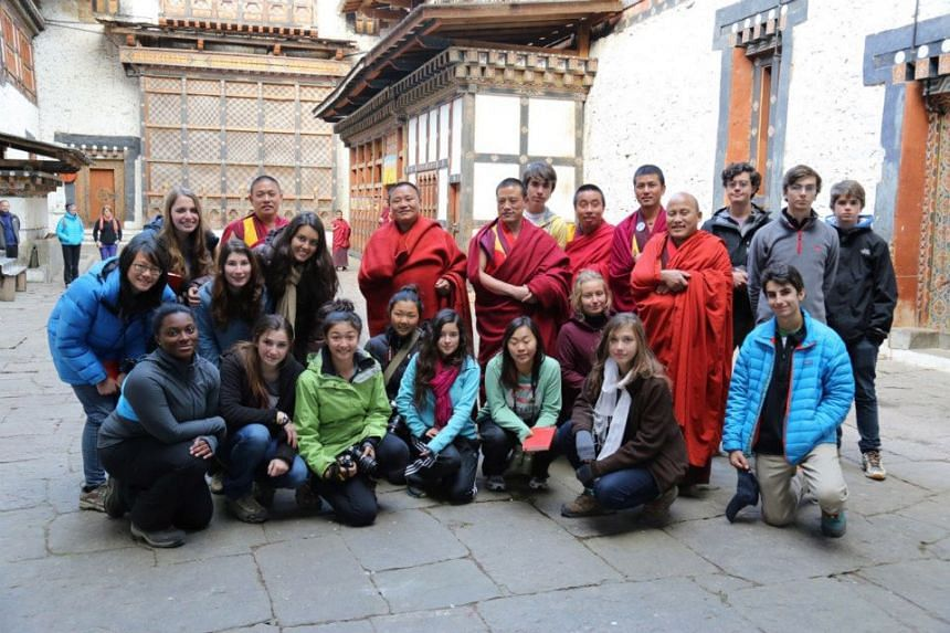 Students from Think Global School and Buddhist monks gather for a photo inside the Trongsa Dzong in Bhutan.