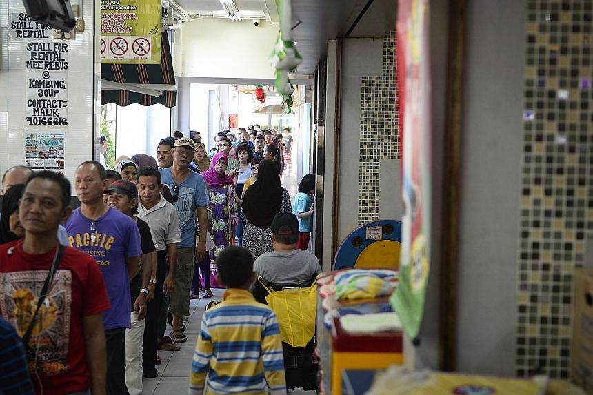 The queue for porridge at Mr Elangovan's Bedok North coffee shop yesterday. For the last decade, he has distributed porridge to hundreds of people every day during Ramadan.
