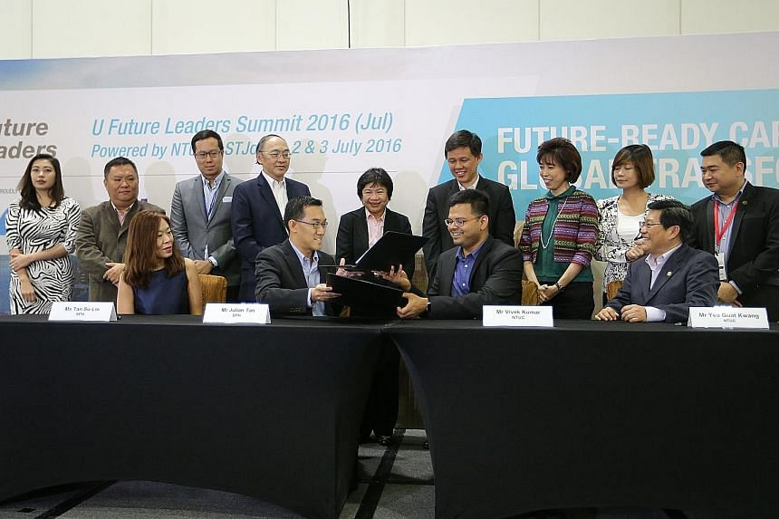 The MOU was signed by Mr Julian Tan, executive vice-president of SPH Digital, and Mr Vivek Kumar, director of U Associate and U Future Leaders, NTUC (seated, centre). It was observed by SPH CEO Alan Chan (standing, fourth from left) and NTUC secretar