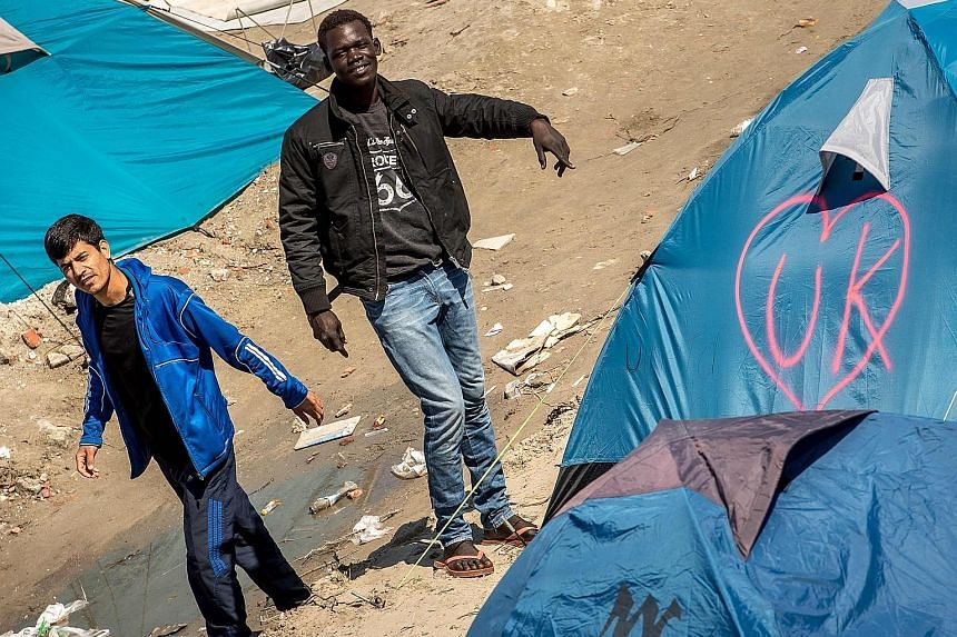 "Migrants in the ""Jungle"" camp in Calais, France, with a tent tagged ""UK"" in a heart-shaped logo. The Leave campaign emphasised the high levels of migration as a key factor in the Brexit referendum. Outgoing Prime Minister David Cameron says immigrati"