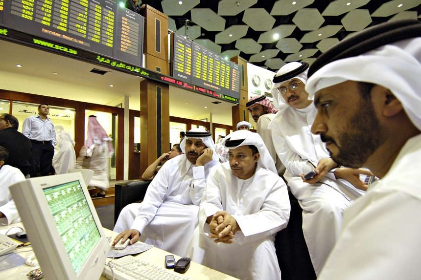 Traders in traditional Emirati dress looking at monitors at the Dubai Financial Market