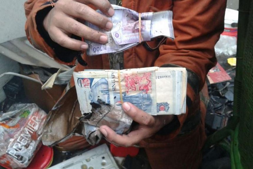 Fireman Hairul Mat Nin, 33, with the cash and valuables he found on the second floor of the shop.